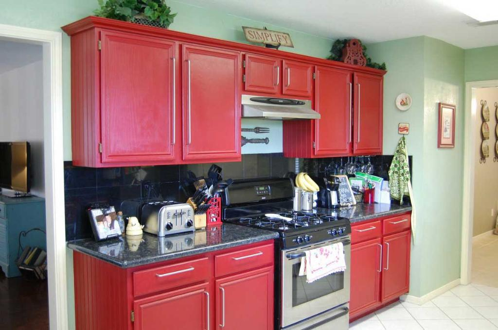 simple-small-metal-gasstove-between-big-red-kitchen-cabinets-close-green-wall-paint