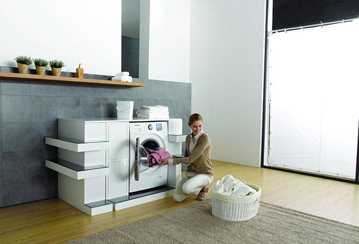 Женщина загружает шторы в стиральную машину