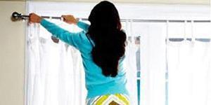 Девушка вешает прозрачные занавески