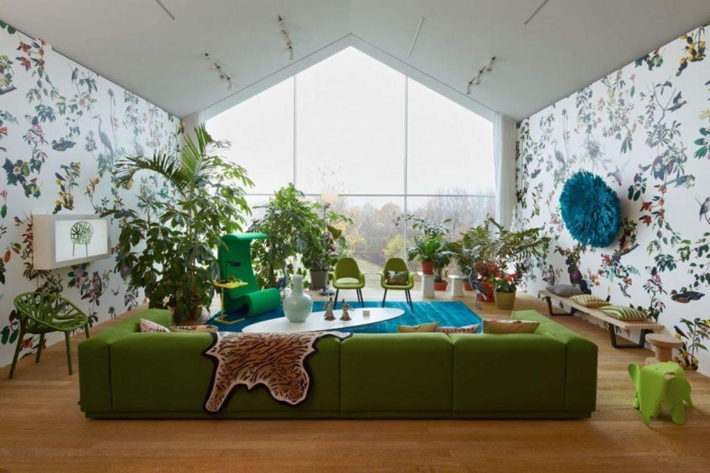 Фото комнаты с большим витражным окном и зелёным диваном