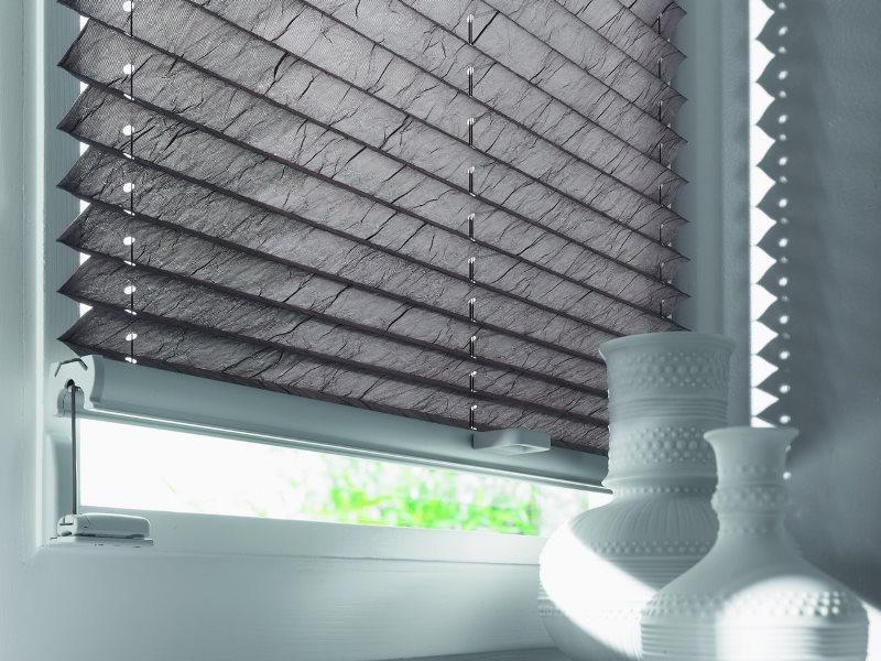 серые шторы плиссе на пластиковом окне
