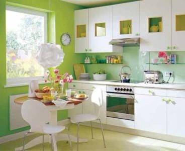 Белый кухонный гарнитур на фоне зеленых стен