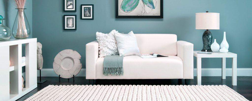 Белый диван на фоне голубой стены