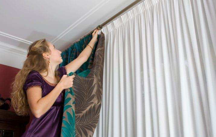 девушка вешает штору на окно