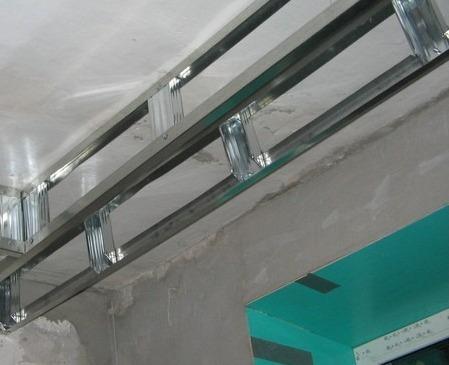 Короб собирают преимущественно из направляющих профилей для гипсокартона. Сначала направляющие профиля закрепляют на потолок с шагом 50 см. Затем делают отводы на стену длиной 7 – 10 см и к ним крепят горизонтальные направляющие, которые образуют горизонтальную часть короба. Чтобы горизонтальные профили не прогибались под весом ГКЛ, их дополнительно закрепляют к профилям, которые установлены на потолке, перемычками. Перемычки изготавливаются из потолочного профиля. Они устанавливаются с шагом 60 см. После сборки каркаса короб зашивают гипсокартоном.