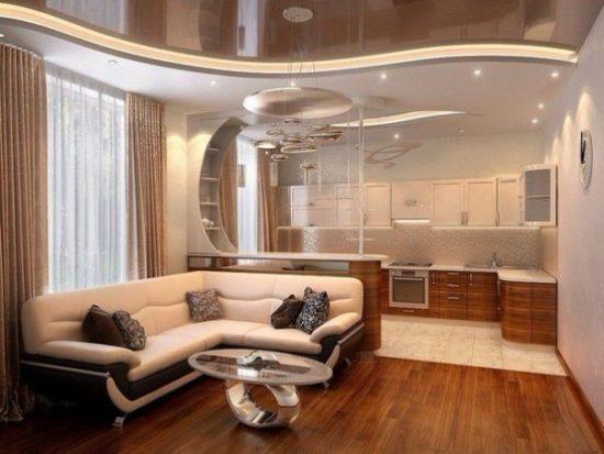 Гостиная с диваном в цвете слоновая кость и темный кухонный гарнитур в одном пространстве