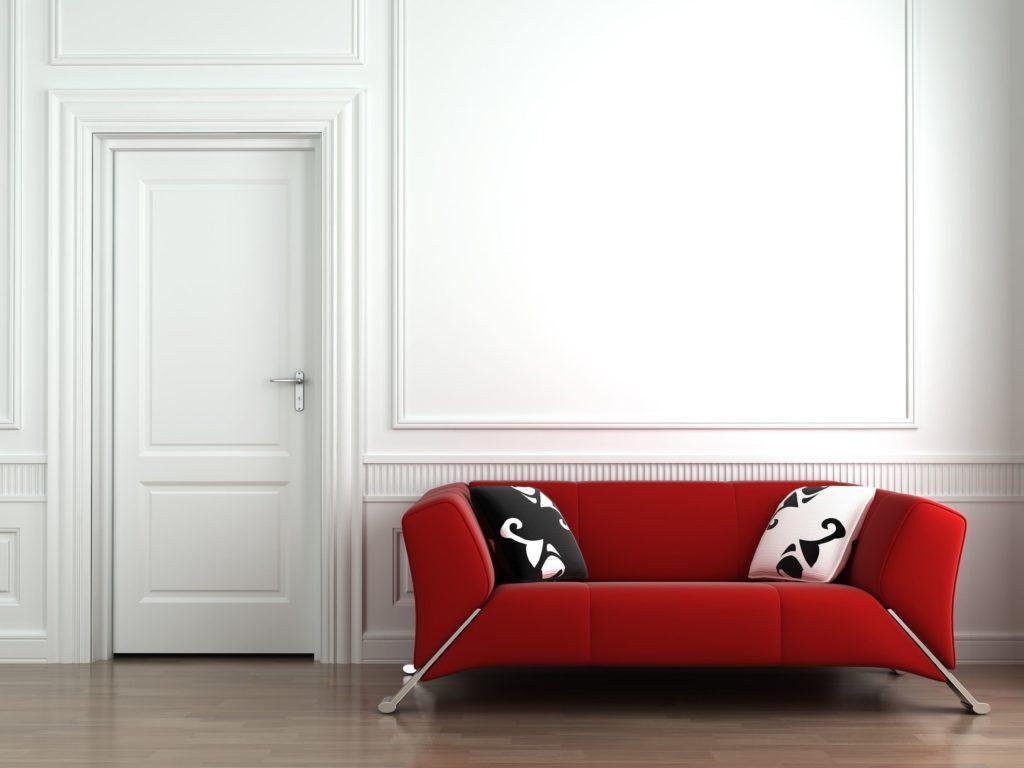Дизайнерский прямой красный диван у белой стены