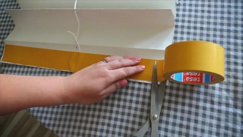 Протянутую сквозь все жалюзи веревку закрепляем при помощи двухстороннего скотча к складке, которая планируется как верхняя
